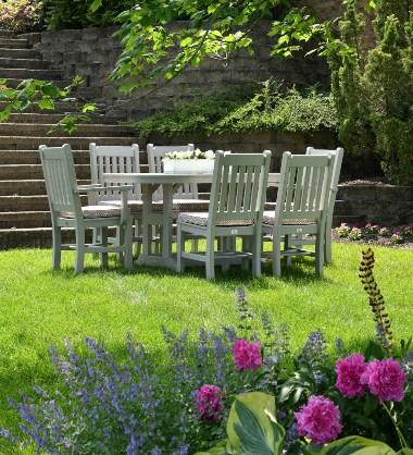 Sto i stolice bele boje na travi u dvorištu